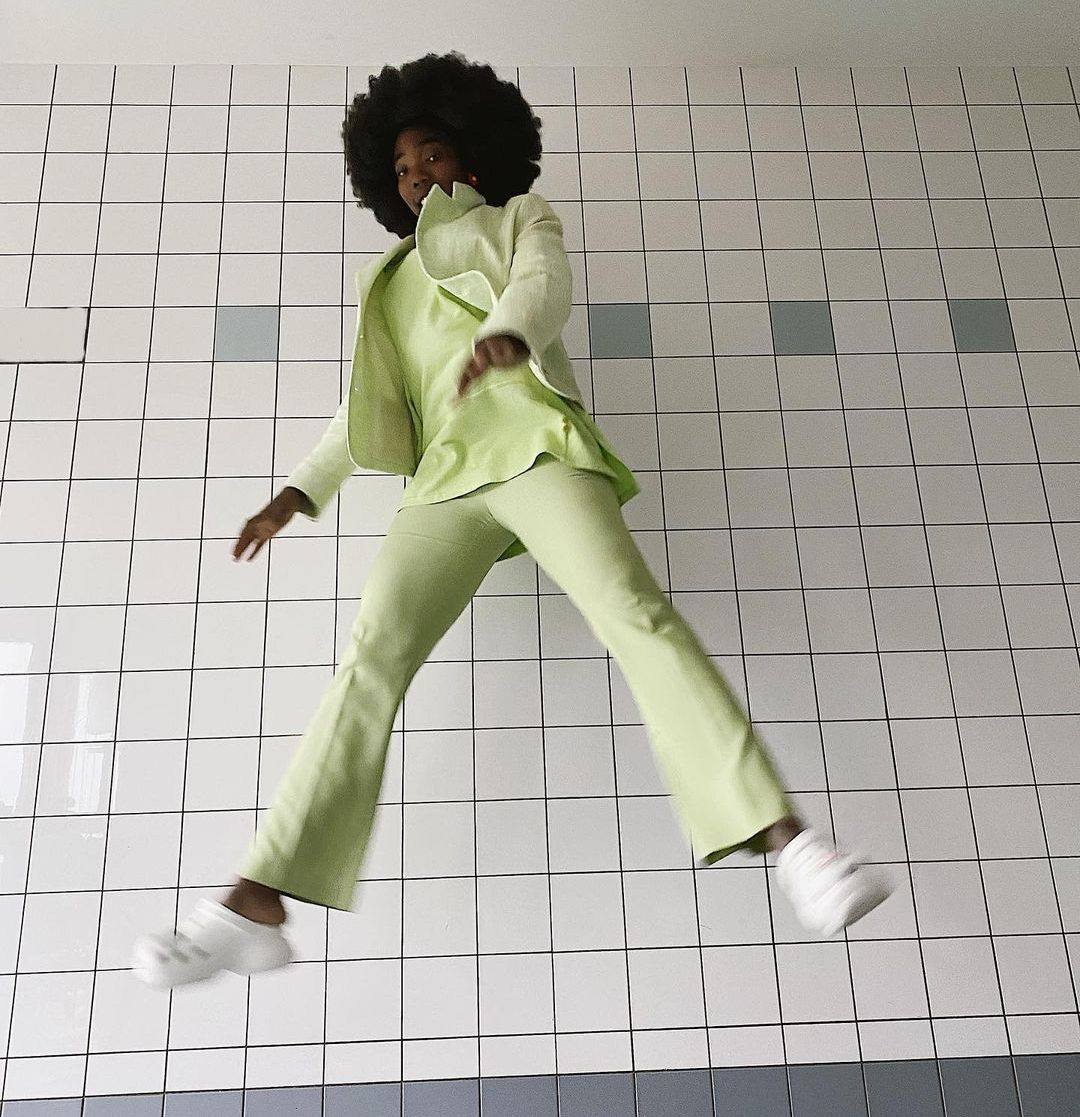 Black woman wearing green suit and clogs jumping in the air