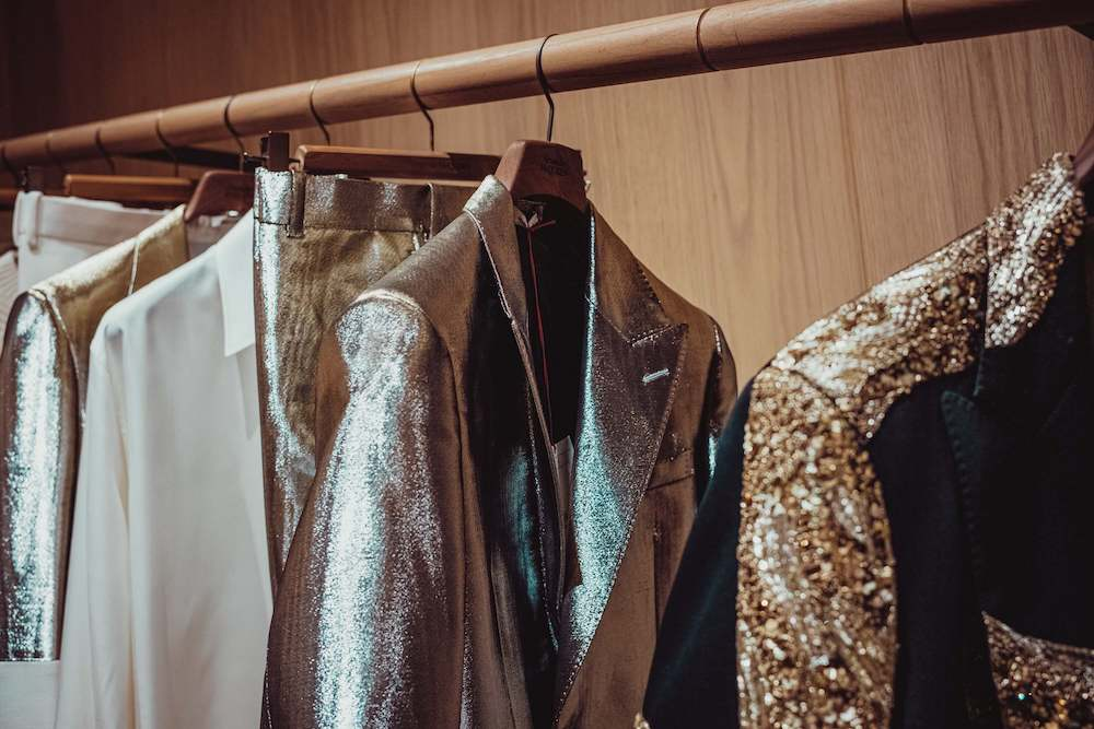 Metallic suit and glitter jacket hanging in wardrobe