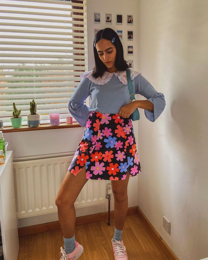 Influencer @anishakalsi wearing a blue sweater with an oversized collar and a floral mini-skirt with blue socks and pink trainers
