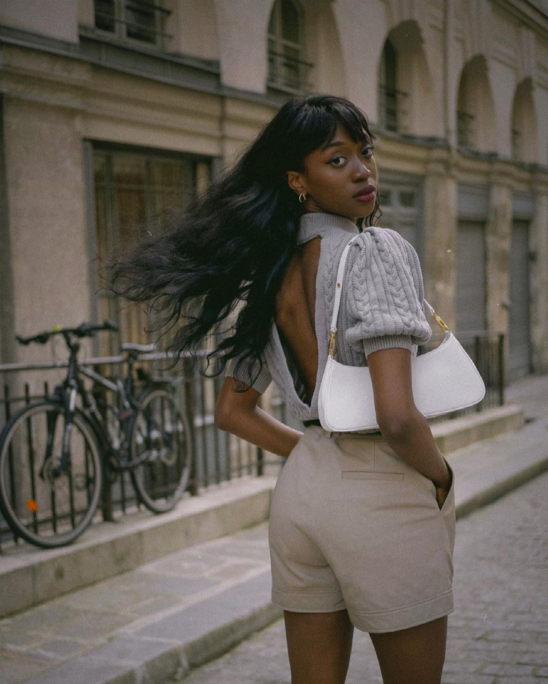 Black woman wearing a backless sweater in grey, beige shorts and a white shoulder bag looking at the camera