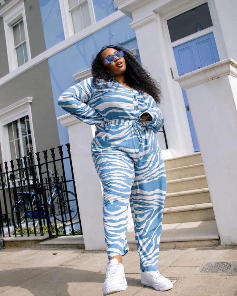 Influencer Lauren Nicole wearing a blue and white tiger print jumpsuit with blue rectangle sunglasses and trainers standing in a street in front of a blue door and painted blue house.