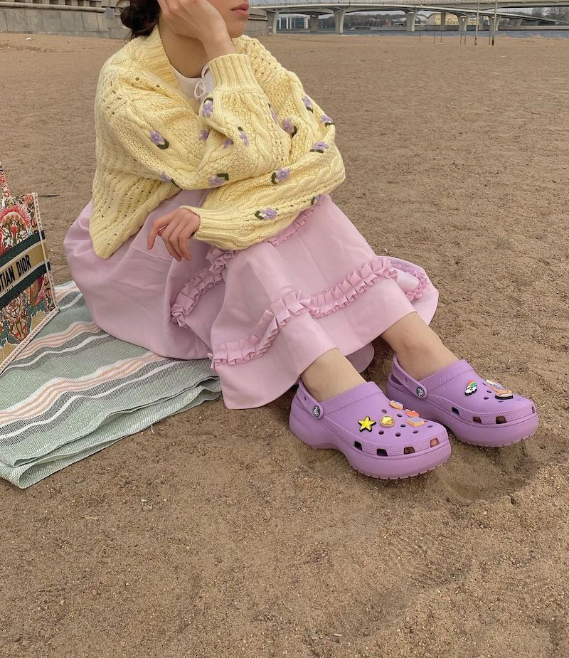 Woman wears lilac crocs, a lilac skirt and yellow cardigan on the beach.