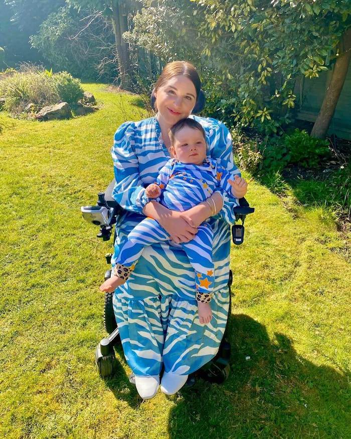 A woman sits in her wheelchair in garden holding her baby. Both are wearing blue zebra print, with Sophie in a dress and her baby in a onesie.