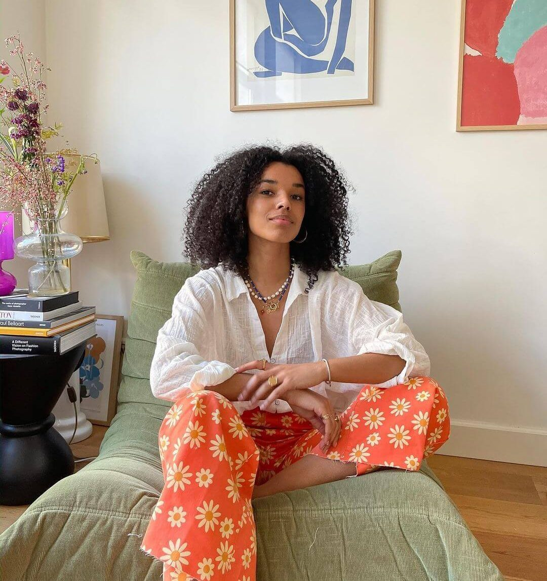 Influencer fiahamelijnck in red floral jeans and a white blouse sitting in her living room with framed pictures in the background