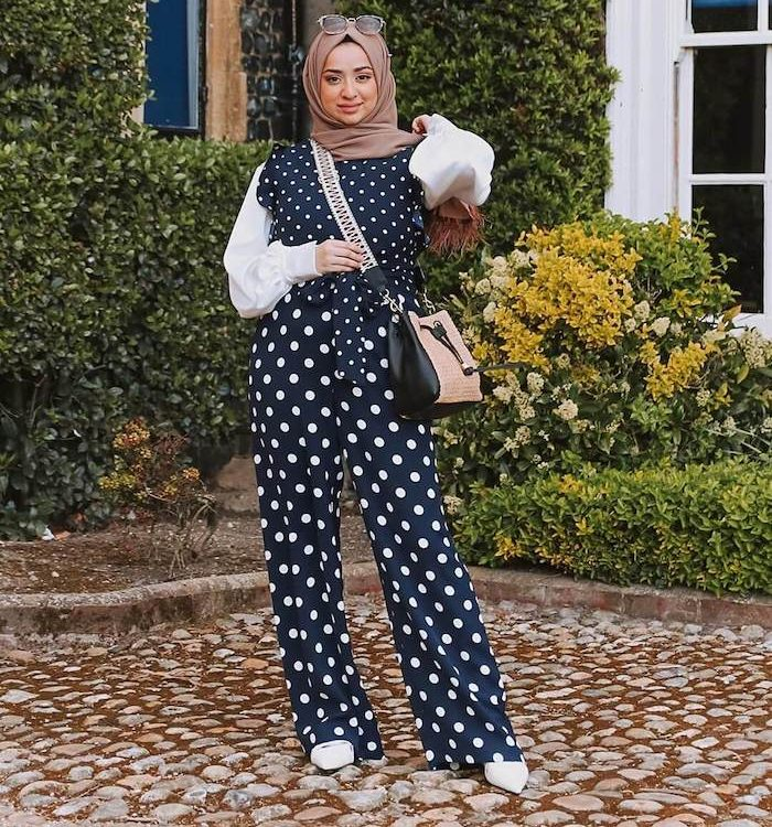 Woman wearing beige hijab, navy polka dot jumpsuit, cross body bag and white boots standing in front of house with green plants.