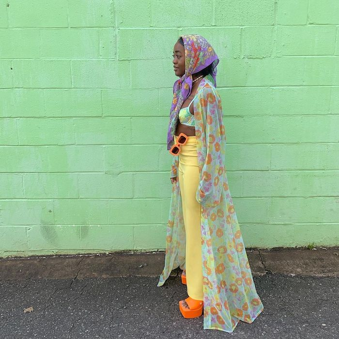 Woman / influencer @nxcv.a wearing floral headscarf, floral sheer jacket, a blue printed bra, yellow trousers and orange mules standing in front of a green wall.