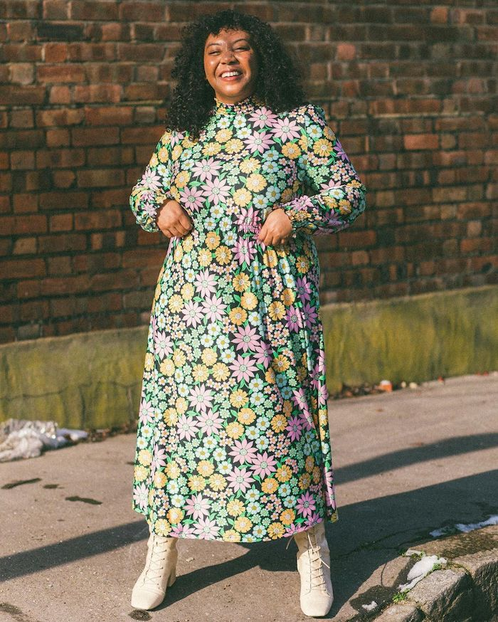 Nicole Ocran wearing a pink, green and yellow floral dress with white lace-up boots.