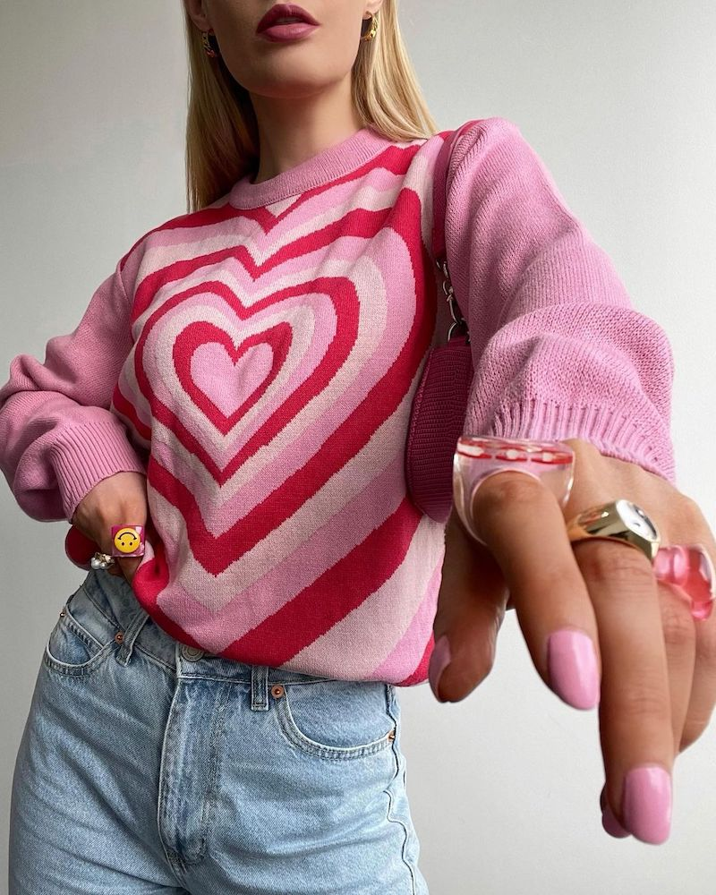 A blonde woman wears pink heart print jumper and jeans and points to the camera. She's wearing resin rings and has pink nails.