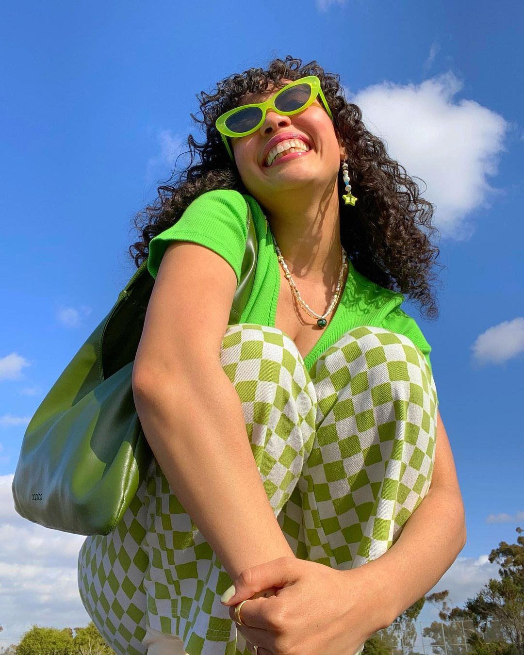 Jazmine Rogers wears green rectangle sunglasses, neon green t-shirt, checkerboard jeans and a green bag and smiles at the camera with blue skies in the background